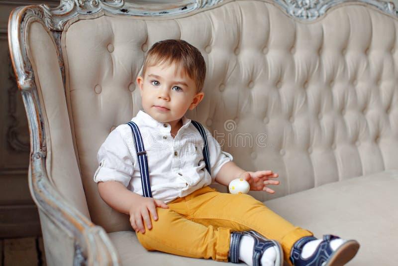 Liten mycket gullig pojke i gulingflåsanden och hängslen som sitter på a arkivfoton