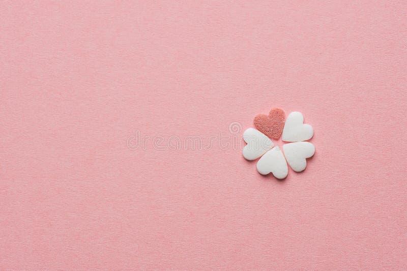 Liten nätt blomma som göras av hjärta Shape Sugar Candy White och röda stänk på bakgrund för pastellfärgade rosa färger Dag för v arkivbilder