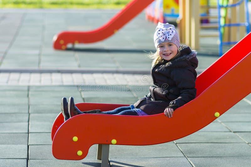 Liten nätt flicka för barn som spelar på lekplats utomhus royaltyfri fotografi