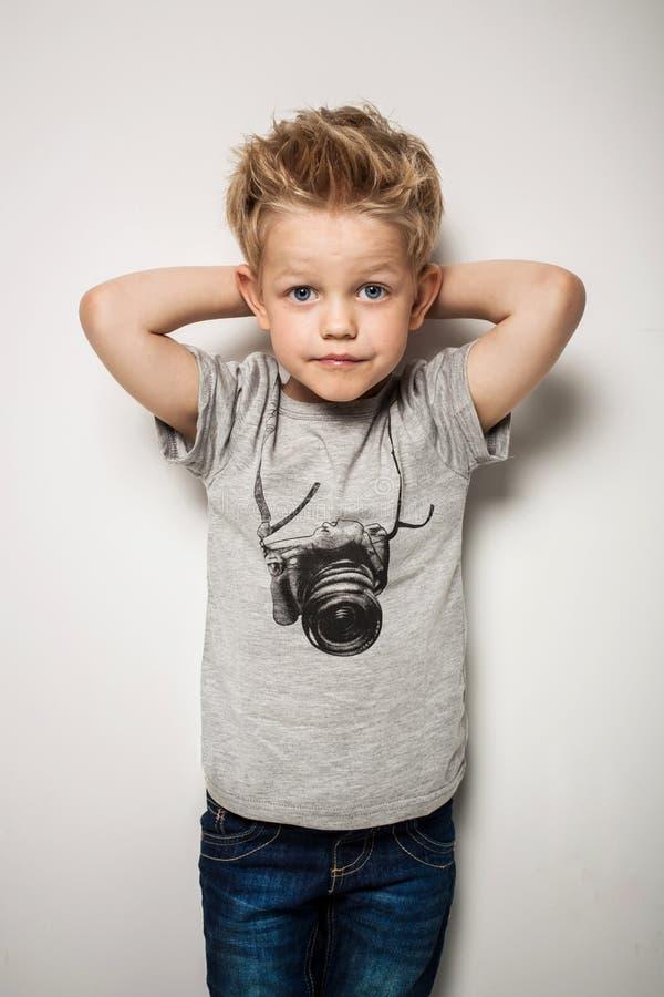 Liten nätt pojke som poserar på studion som en modemodell arkivfoton