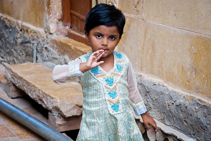 Liten nyfiken flicka i härlig traditionell kläder i Jaisalmer, Rajasthan, Indien arkivfoto