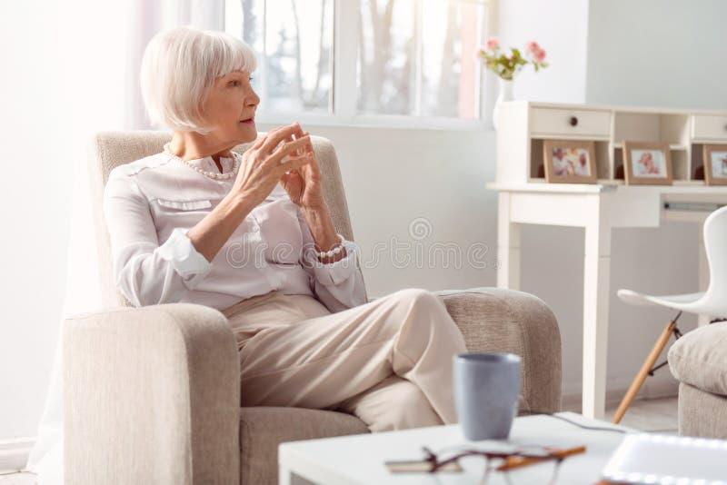 Liten och nätt äldre dam som är djup i tanke i hennes vardagsrum arkivfoton