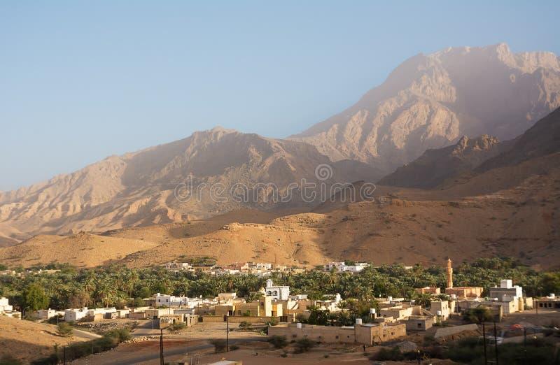 Liten omansk by under bergen och nära Qurayyat Oman royaltyfria bilder