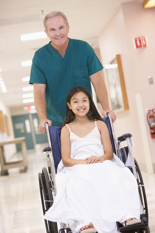 liten ordningsam skjutande rullstol för flicka arkivfoto