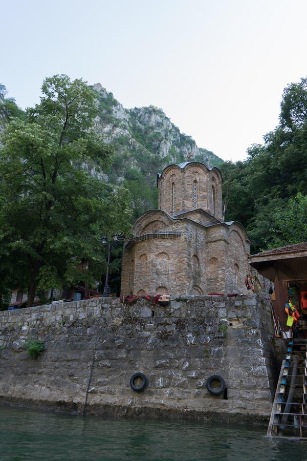Liten ortodox kyrka med gamla tegelstenväggar under berget med träd och den stora skogfloden med den religiösa dragningen i Matka royaltyfri bild