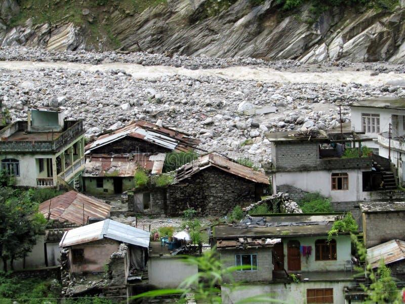 Liten by på banken av den Alaknanda floden i Himalayas, Indien arkivfoton