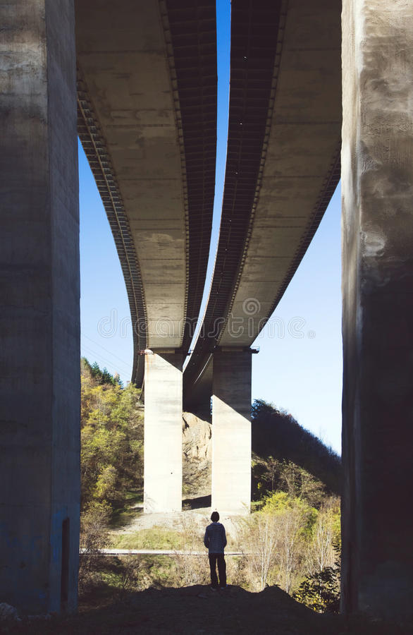 Liten person under en stor bro royaltyfri foto