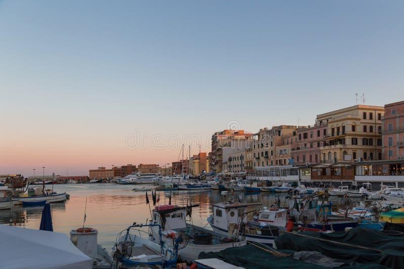 Liten pikturesk stadshamn vid solnedgång Anzio, regionen Latium, Italien Fiskefartyg, små yachter på vacker kvällsbakgrund arkivbilder