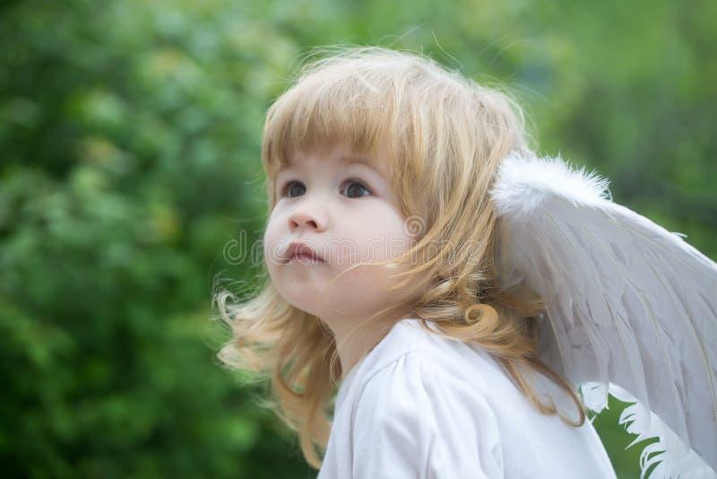 Liten pojke i ängelvingar arkivbild
