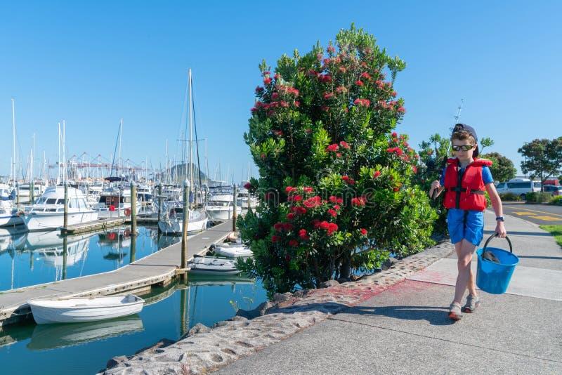 Liten pojke med gående fiska för metspö och för hink royaltyfria foton