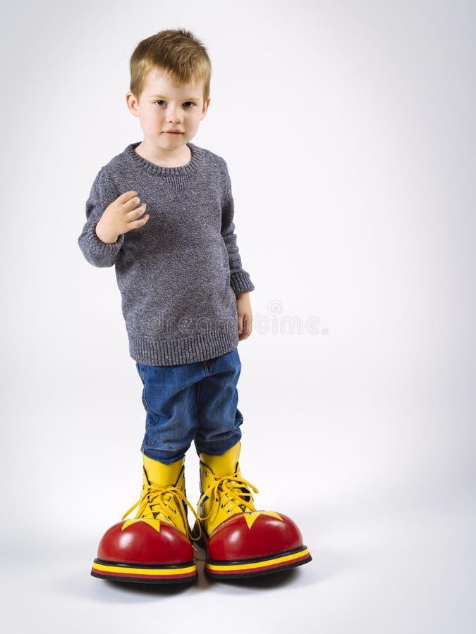 Liten pojke med stora clownskor royaltyfri bild