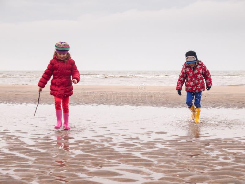 Liten pojke och flicka som paddlar på stranden arkivbilder