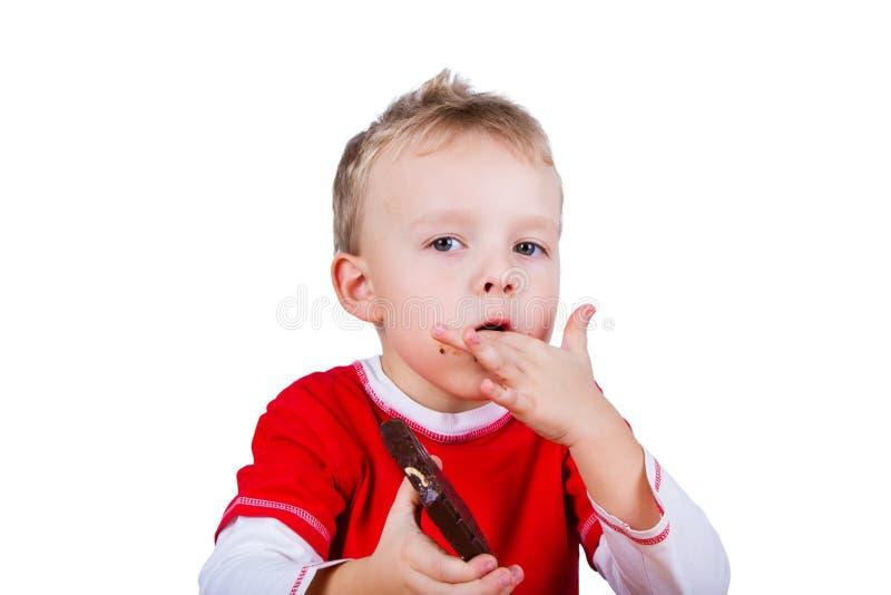 Liten pojke som äter den hela stången av choklad royaltyfri foto