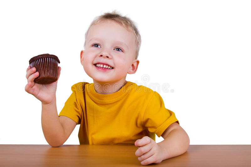 Liten pojke som äter en chokladmuffin arkivfoton