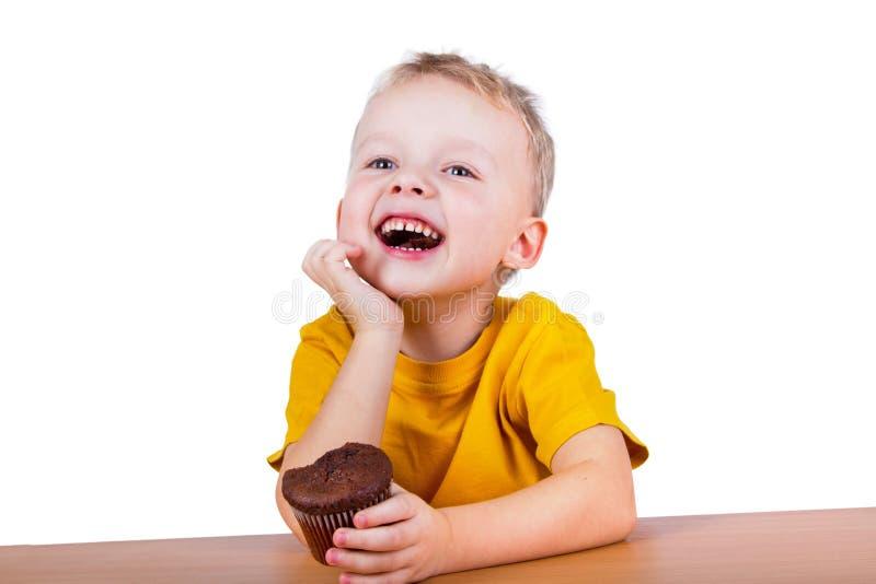 Liten pojke som äter en chokladmuffin arkivbilder