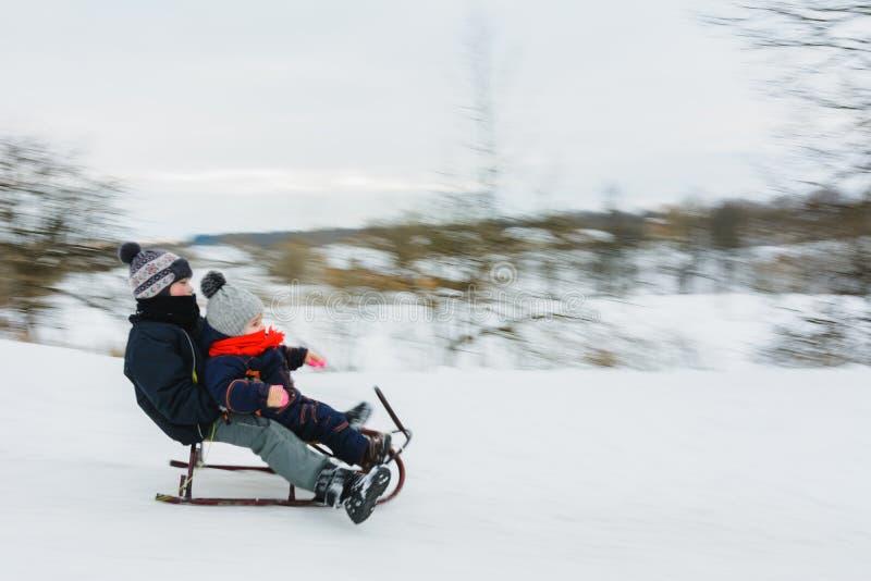 Liten pojke som sledding på vintertid bakgrundsblur suddighetdde rörelse för låsfrisbeebanhoppning till royaltyfria foton