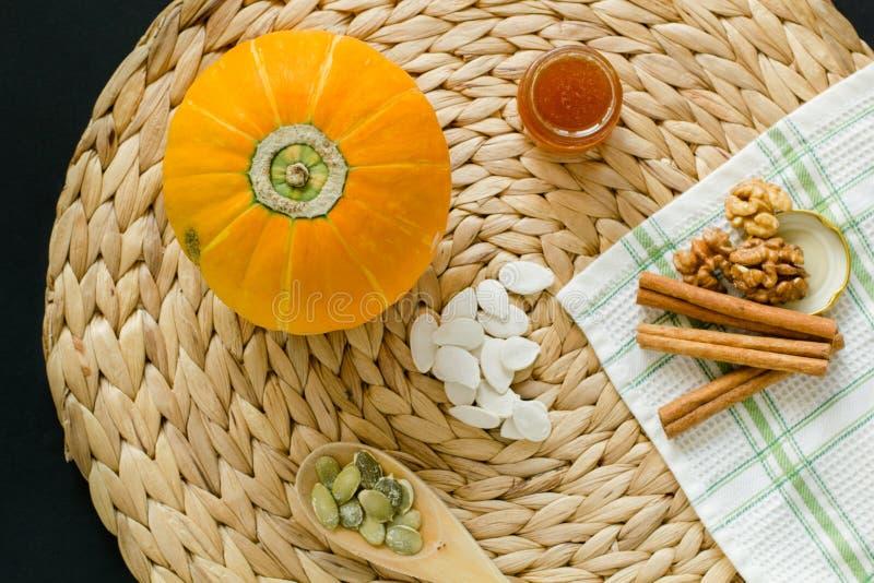 Liten pumpa med frö, skalade frö i träskeden, litet exponeringsglas kan av honung, valnötter och kanelbruna pinnar på en cirkel m arkivbild