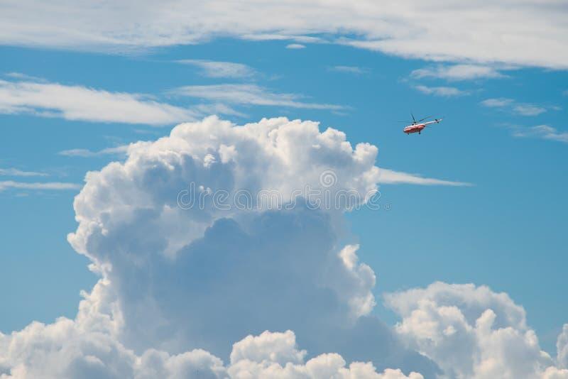 Liten röd helikopter i stora moln royaltyfri fotografi