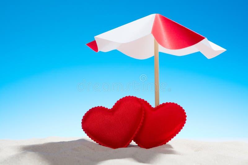 Liten röd hjärta två under paraplyet på stranden royaltyfri foto