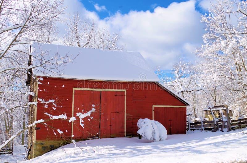 Liten röd ladugård i snön royaltyfria foton