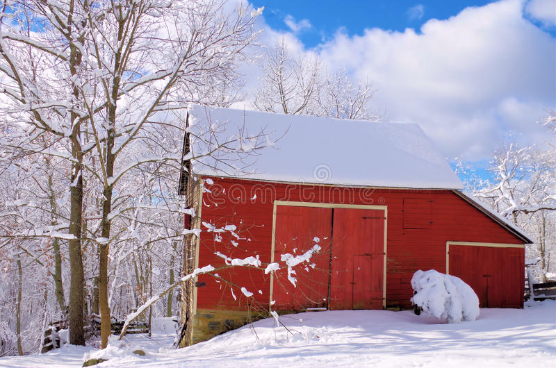 Liten röd ladugård i snön arkivfoto