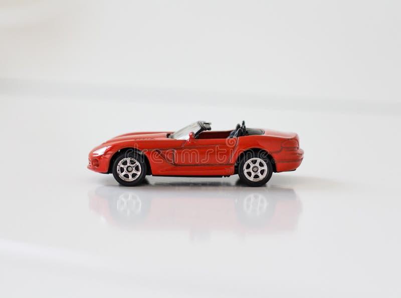 Liten röd leksaksportbil på en vit bakgrund royaltyfria foton