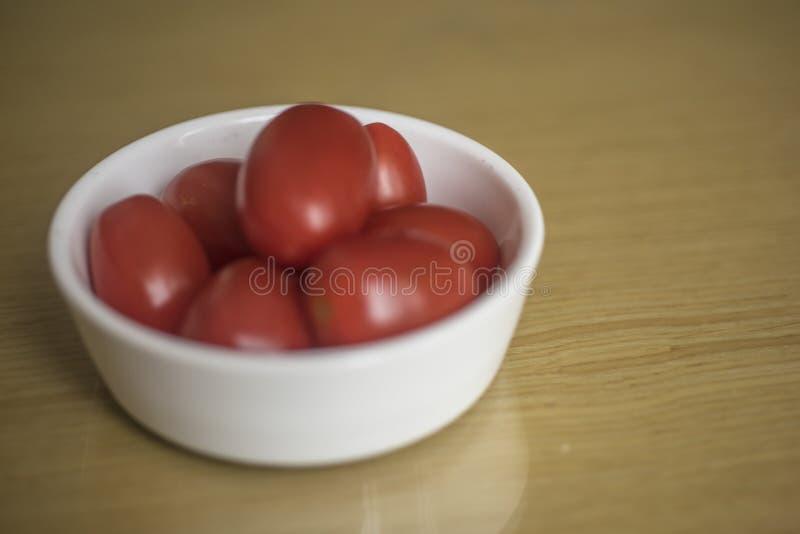 Liten röd tomatfrukt på en keramisk platta för liten vit runda arkivbild