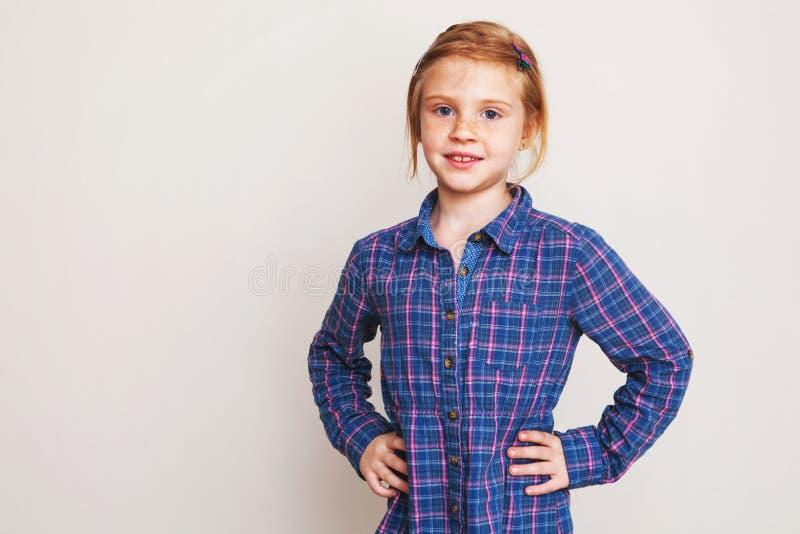 Liten rödhårig manflicka i den blåa plädskjortan som poserar mot väggen royaltyfria foton