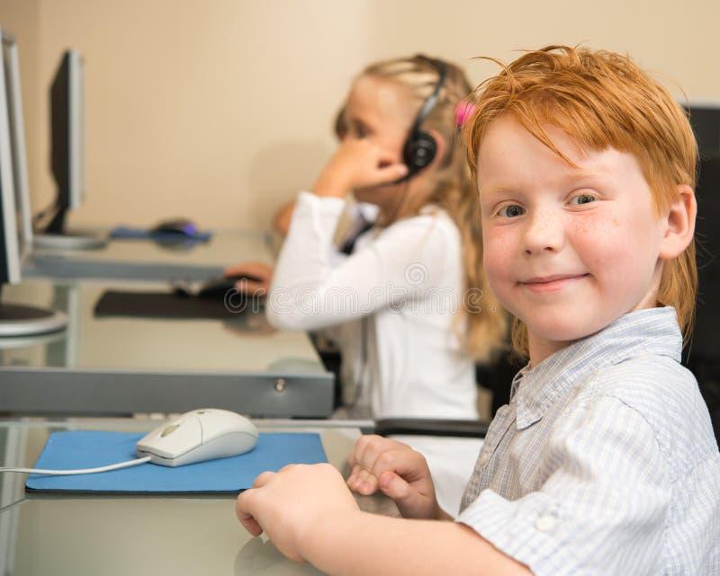 Liten rödhårig manskolpojke framme av den skrivbords- datoren arkivbilder