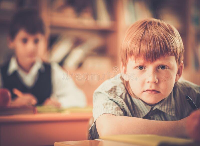 Liten rödhårig manskolpojke under kurs royaltyfri foto