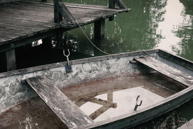 Liten roddbåt med läckan på landningetappen arkivbild