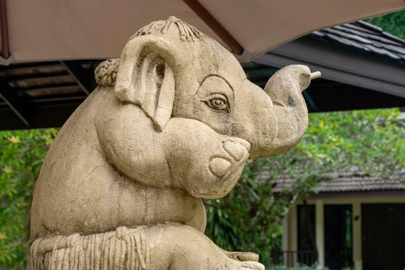 Liten rolig elefant, skulptur som sitter under ett paraply royaltyfria bilder