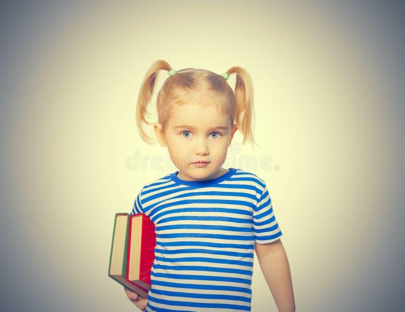Liten rolig flicka med böcker royaltyfri bild