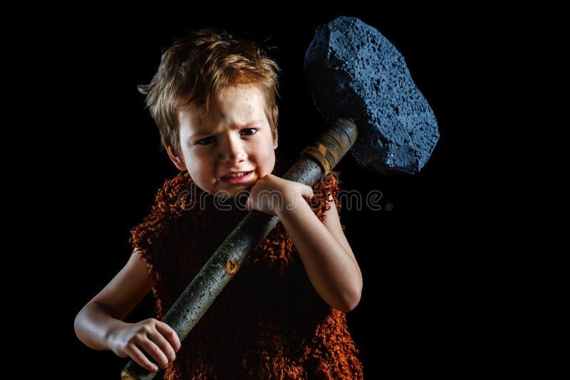 Liten rolig ilsken krigarepojke Neanderthal eller en cro-Magnon Forntida grottmänniska som är forntida royaltyfri fotografi