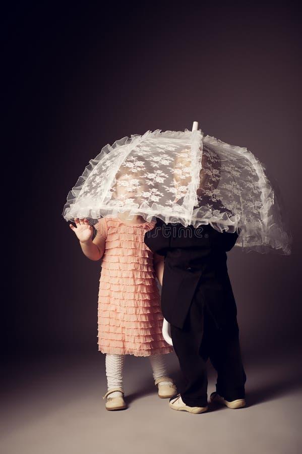 Liten rolig pojke och flicka under paraplyet royaltyfri foto