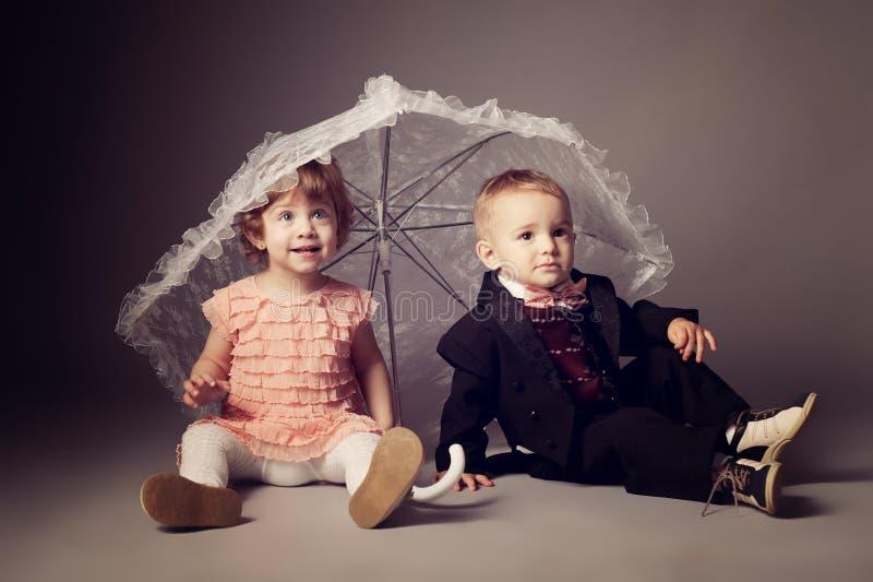 Liten rolig pojke och flicka under paraplyet royaltyfria bilder