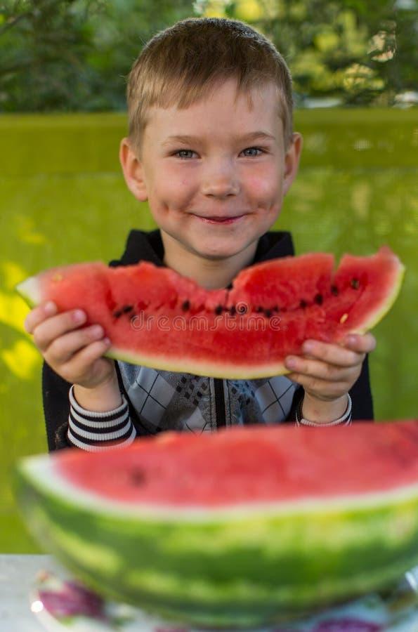 Liten rolig pojke som äter vattenmelon Lyckligt arkivfoto