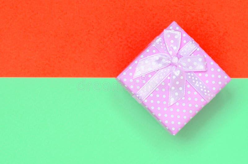 Liten rosa lögn för gåvaask på texturbakgrund av pastellfärgad turkos för mode och papper för röda färger arkivbilder