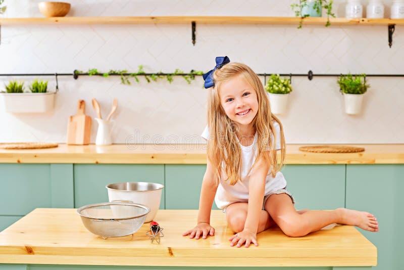 Liten söt liten flicka med blont hår och vit en tröja som hemma sitter i köket arkivfoto