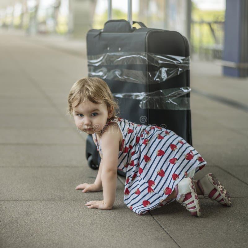 Liten söt flicka med en stor resande resväska på öde rommar arkivbilder