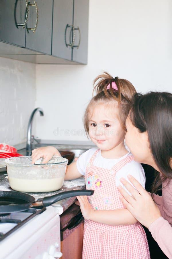 Liten s?t flicka och hennes modersm?fiskpannkakor p? den traditionella ryska feriekarnevalet Maslenitsa Shrovetide royaltyfria foton