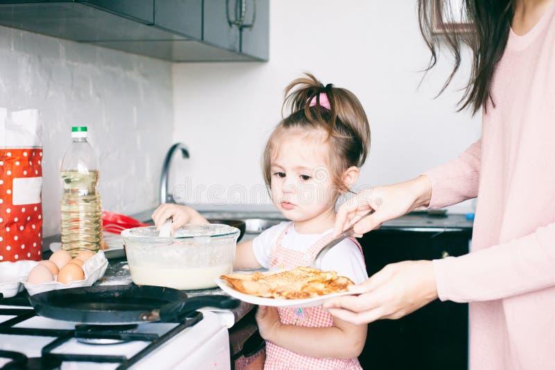 Liten s?t flicka och hennes modersm?fiskpannkakor p? den traditionella ryska feriekarnevalet Maslenitsa Shrovetide royaltyfri foto