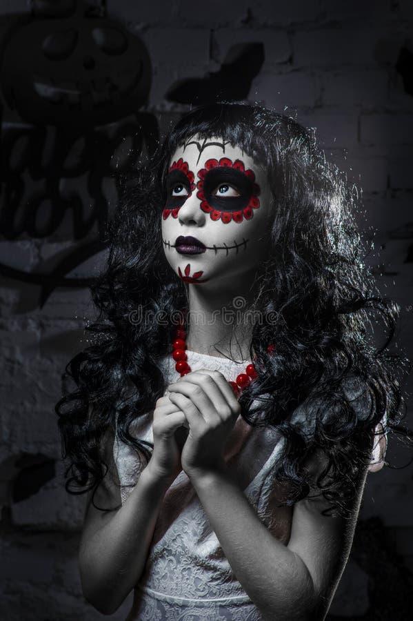 Liten santa muerteflicka med svart lockigt hår arkivfoto