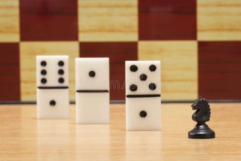 Liten schackhäst och tärning för att spela domino royaltyfria foton