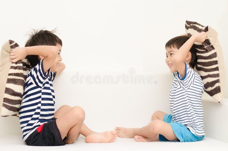 Liten siblingpojke som spelar kuddestridighet på soffan arkivbild