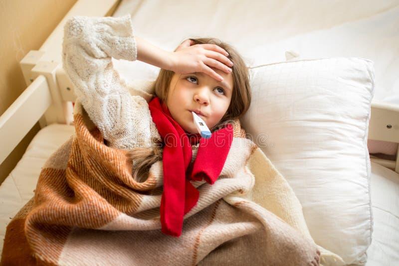 Liten sjuk flicka som mäter temperatur och innehavhanden på huvudet arkivbild