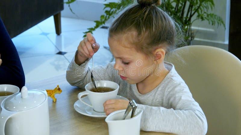 Liten sked för ryssflickainnehav och stiring socker i te på restaurangen royaltyfri foto