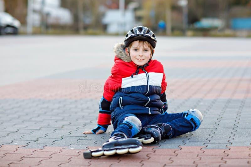 Liten skolaungepojke som åker skridskor med rullar i staden barn i skyddssäkerhetskläder Aktiv skolpojkeframställning arkivfoto