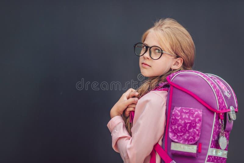Liten skolflicka med en ryggsäck royaltyfri foto