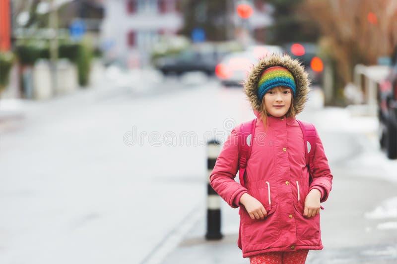 Liten skolflicka med ryggsäcken i vinter royaltyfri bild